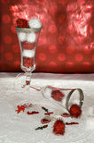 Valentine Champagne Flutes. Two champagne flutes with red and white balls on lace with red background and valentine decorations Stock Image