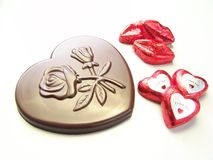 Valentine chocolate celebration. Valentine day celebrations with Heart and lips chocolates wrapped in red paper and a big heart chocolate with embossed flowers Royalty Free Stock Images