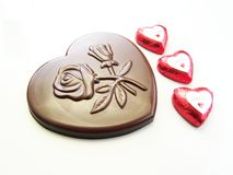 Valentine chocolate celebration. Heart and lips chocolates wrapped in red paper and a big heart chocolate with embossed flowers on it Stock Images