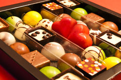 Valentine chocolates. Box full of sweets with heart-shaped chocolates in the middle. A Valentine's Day gift Stock Images