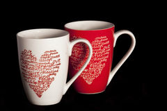 Valentine coffee cups. Coffee cups with hearts on a black background Royalty Free Stock Photography