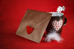 Valentine concept, love letter, and a heart cup on a red background. Valentine`s day celebration with romantic items: sealed love letter, and a heart cup on a Stock Image