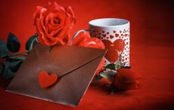 Valentine concept, love letter, rose and a heart cup on a red background. Valentine`s day celebration with romantic items: sealed love letter, a rose, a heart Stock Photos
