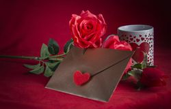 Valentine concept, love letter, rose and a heart cup on a red background. Valentine`s day celebration with romantic items: sealed love letter, a rose, a heart Royalty Free Stock Photos