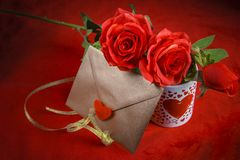 Valentine concept, love letter, rose and a heart cup on a red background. Valentine`s day celebration with romantic items: sealed love letter, a rose, a heart Royalty Free Stock Photography