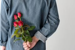 Valentine concept, Man holding red roses hiding on back on white. Background Stock Image