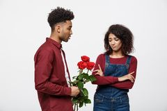 Valentine concept - young african american woman upset and ignore rose from her boyfriend. Valentine concept - young african american women upset and ignore Stock Photos