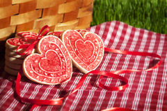 Valentine Cookies Picnic Basket. Heart shaped Valentine cookies on red and white checked cloth and leaning against wicker picnic basket, green grass in Stock Image
