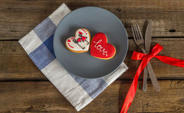 Valentine cookies on a plate and cutlery on a wooden background Royalty Free Stock Photos