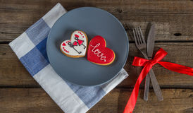 Valentine cookies on a plate and cutlery on a wooden background Royalty Free Stock Image