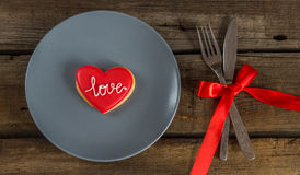Valentine cookies on a plate and cutlery on a wooden background Royalty Free Stock Photo