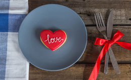 Valentine cookies on a plate and cutlery on a wooden background Royalty Free Stock Photography