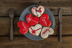 Valentine cookies on a plate and cutlery on a wooden background Royalty Free Stock Images