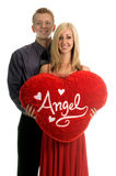 Valentine Couple. Young Valentine Day couple in love. Woman looking at camera and holding a large heart shaped pillow that says Angel Stock Photography