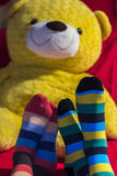 Valentine couple feet with a teddy bear on background. Colored socks on Valentine couple feet with a teddy bear on background Royalty Free Stock Images