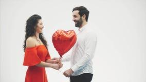 Valentine Couple La ragazza di bellezza ed il suo ragazzo bello che tengono il cuore hanno modellato l'aerostato e baciare Allegr video d archivio