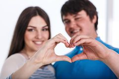 Valentine Couple. Portrait of Smiling Beauty Girl and her Handsome Boyfriend making shape of Heart by their Hands Stock Image