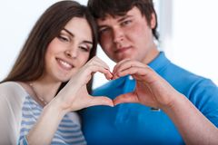 Valentine Couple. Portrait of Smiling Beauty Girl and her Handsome Boyfriend making shape of Heart by their Handsng Stock Photo