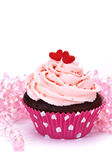 Valentine Cupcake. Chocolate cupcake with pink buttercream frosting decorated with sprinkles and candy hearts on a white background stock image