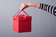 Valentine-daggift in vrouwenhand op blauwe achtergrond Het concept vakantiegift royalty-vrije stock foto