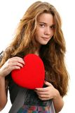 Valentine day. Portrait of a young woman holding a red heart and day dreaming over white background Stock Photography