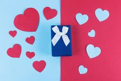 Valentine day background with blue gift box and hearts on devided colored background. Valentine day background with blue gift box and hearts on devided colored Royalty Free Stock Photography