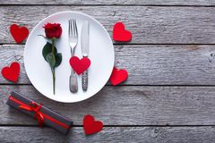 Valentine day background, cutlery with rose on plate on wood. Valentine day background. Top view of restaurant wooden table with rose and cutlery on plate, paper Stock Image