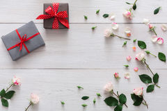 Valentine day background, gift boxes and flowers on white wood. Valentine background with pink rose flowers frame and gift boxes with copy space on white rustic Royalty Free Stock Photo
