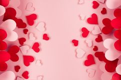 Valentine day background of many different paper hearts on pink soft background. Copy space.