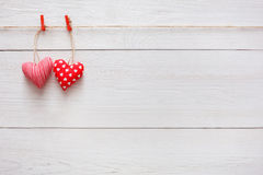 Valentine day background, pillow hearts couple on wood, copy space. Valentine background with sewed pillow diy handmade hearts couple on red clothespins at royalty free stock photo