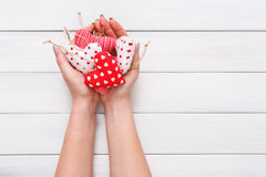 Valentine day background, pillow hearts in female hands Royalty Free Stock Images