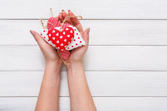 Valentine day background, pillow hearts in female hands Stock Image
