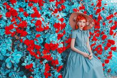 Valentine Day background. Spring blooming rose flower garden. Perfect lady with red lips in dress. Summer hat. Perfect floral wall. Redhead lady on background stock photography