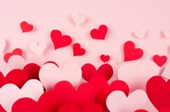 Valentine day background. Stream of fly out red and pink paper hearts on pink color backdrop.