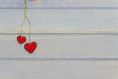 Valentine day banner. Two hearts hanging on a wall. Needlework. Stock Photo