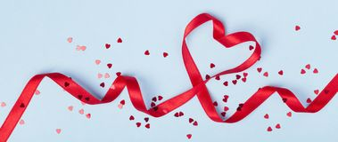 Valentine day card or banner. Red heart of ribbon on blue background. Flat lay. Style stock images