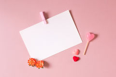 Valentine day composition: stationery / photo template with clamp, small hearts, candy and spring flowers Royalty Free Stock Photo