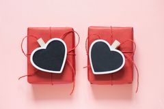 Valentine day composition: two red gift boxes with clothespin as heart with space for text on chalkboard on pastel pink background Royalty Free Stock Images