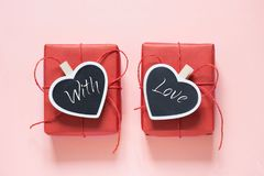 Valentine day composition: two red gift boxes with clothespin as heart with text on chalkboard on pastel pink background. View fro Royalty Free Stock Image