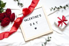 Valentine day concept flat lay on the white blanket with text. Holiday top view card with red roses. Copy space stock photos
