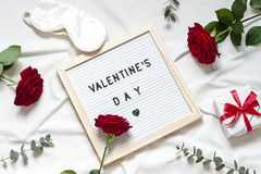 Valentine day concept frame on the white blanket. Holiday top view card with red roses. Copy space royalty free stock images