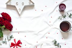 Valentine day concept frame on the white blanket . Holiday top view card with red roses. Copy space stock image