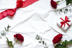 Valentine day concept frame on the white blanket . Holiday top view card with red roses. Copy space stock images