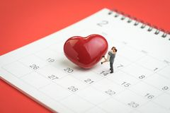 Valentine day concept miniature figures sweet couple standing wi. Th shiny red heart shape on 14th February calendar on red background Stock Photos