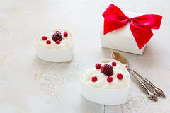 Valentine day decoration, breakfast, yogurt with berries for two in white heart-shaped bowls and gift box on the table Stock Images