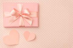 Valentine day decoration. Gift box with ribbon and small coral hearts on living coral background. Top view. Love day flat lay. Valentine day decoration. Gift box stock images