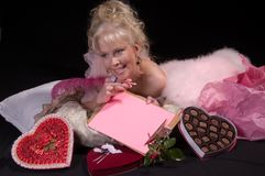 Valentine Day Girl. St. Valentine's day girl writing thank you letters for chocolate gifts Royalty Free Stock Photos