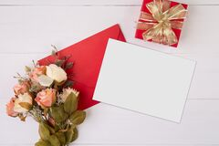 Valentine day, greeting card mockup and letter and flower on wooden table, postcard blank and gift box with romance on desk.