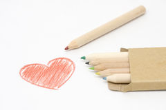 Valentine day heart. A red heart sketched and an assortment of coloured pencils with shadow on white background, ideal for valentine day Royalty Free Stock Photos