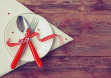 Valentine day, invitation for romantic dinner. White plate, spoon and fork, napkin, heart, old wooden table, vintage style Stock Photo